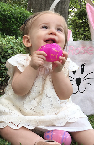 Photo of a baby girl at Easter with 'Rose' stitched on her bag